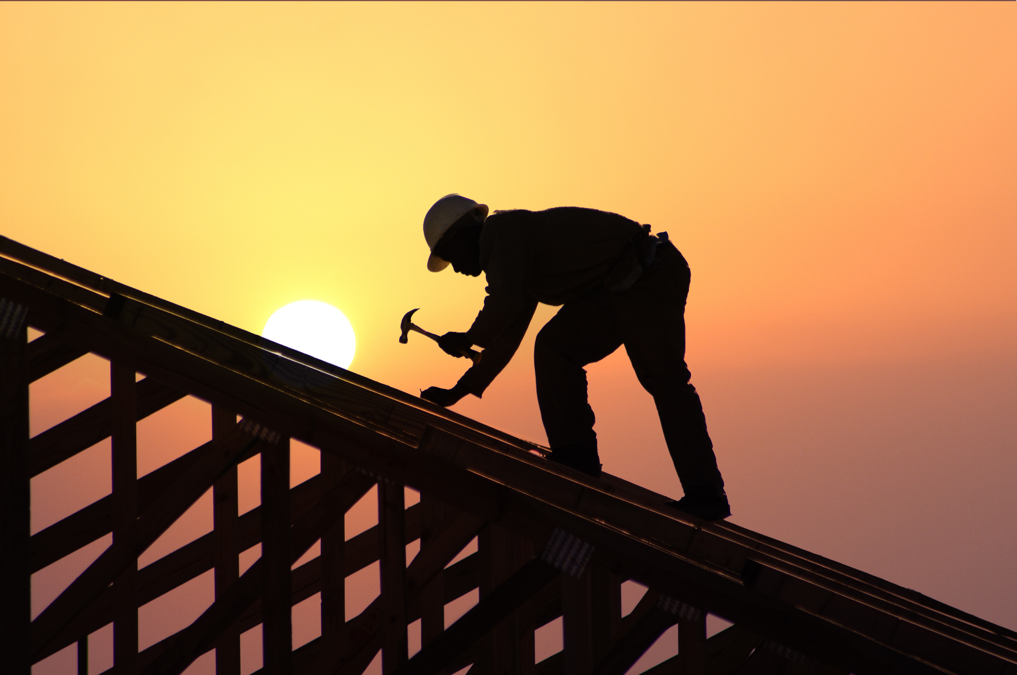 new construction roofing worker on top of house at sunset